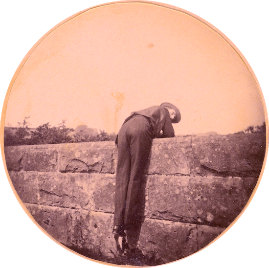 Man in hat, bent over a stone wall (Google Arts Project)